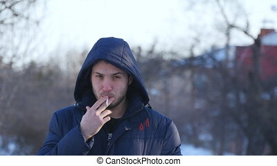 Brutal bearded man smoking a cigarette outdoor.