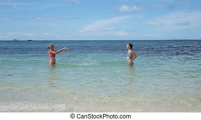 Mother and daughter playing in the sea