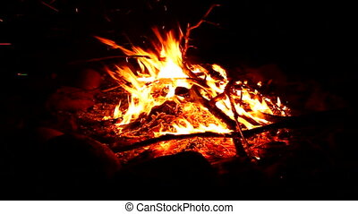 Fire and Sparks - Flames of a cozy campfire flicker in a...