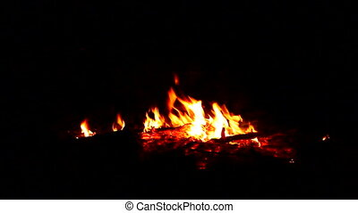 Nighttime Campfire - Campfire burns low as night sets in