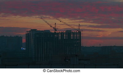 Construction cranes working on background of sunrise -...