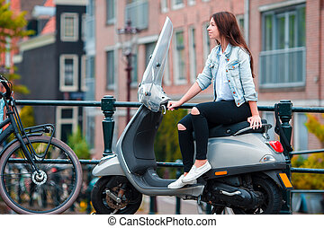 Young girl on a moped on the bridge over the canal in Amsterdam