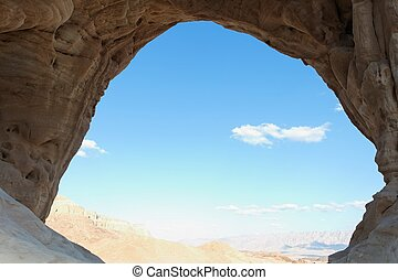 Desert landscape seen through the cave entrance