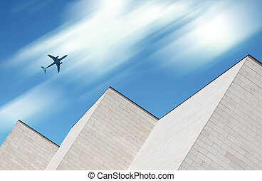 Airplane flying over modern building - Airplane flying over...
