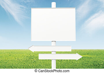 Blank direction signs on a background of green grass and blue sky, mock up
