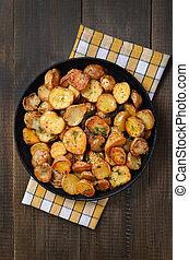 Fried potatoes in a frying pan, top view