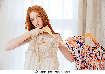 Pensive beautiful young woman deciding what to wear -...