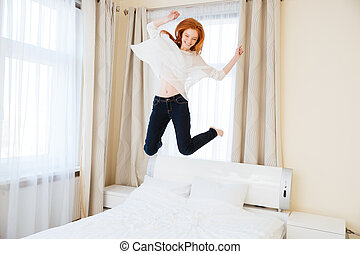 Cheerful woman jumping on the bed - Cheerful young woman...