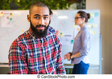 Afro american man standing in office - Young afro american...