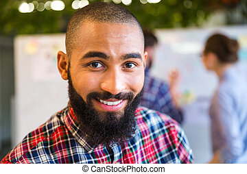 Afro american man looking at camera in office - Smiling afro...