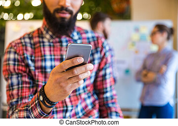 Afro american man using smartphone in office - Cropped image...