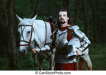 Knight in forest - Knight with white horse wolking in the...