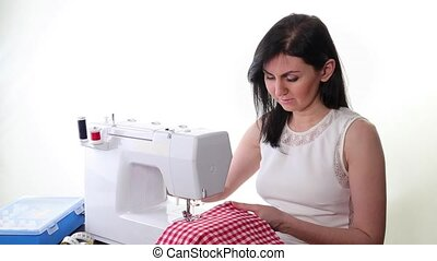 woman sews on the sewing machine on a white background