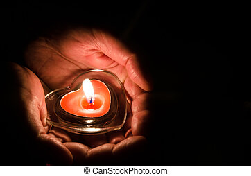 burning candle in hands