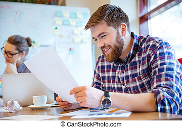 Businessman reading paper in office - Happy young...