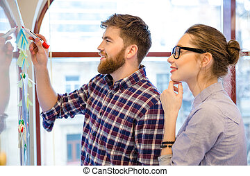 Businessman and businesswoman working with whiteboard -...