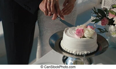 Happy fabulous couple cuts their wedding cake with holding...