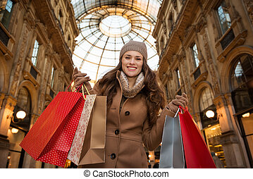 Woman in Galleria Vittorio Emanuele II showing shopping bags...