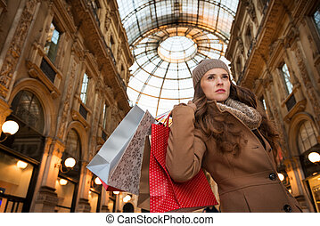 Young woman with shopping bags in Galleria Vittorio Emanuele...