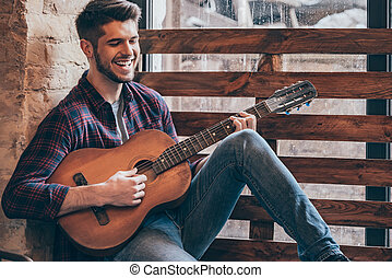 Cheerful guitarist. Cheerful handsome young man playing...