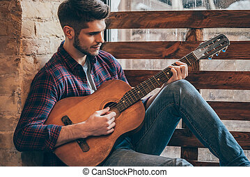 Talented guitarist. Handsome young man playing guitar while...