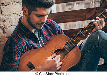 Perfect chord. Close-up of handsome young man playing guitar...