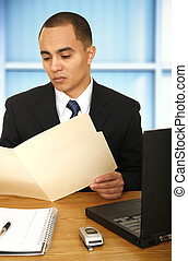 Business Man Reviewing Folder - business man working in his...