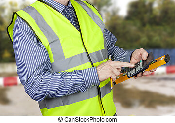 Building surveyor in hi vis vest with calculator and spirit...