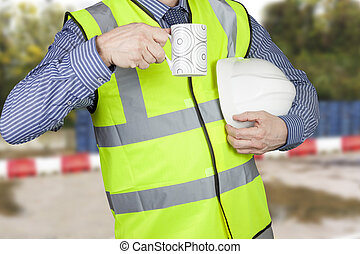 Building surveyor in hi vis with hard hat having a coffee...
