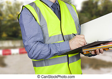 Building surveyor with sprit level writing notes in his...