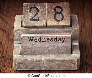 Grunge calendar showing Wednesday the twenty eighth on wood...
