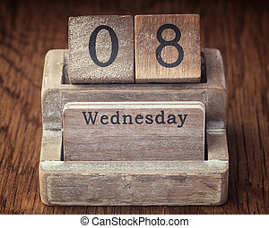 Grunge calendar showing Wednesday the eighth on wood...