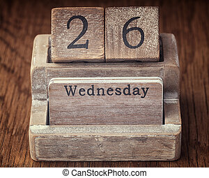 Grunge calendar showing Wednesday the twenty sixth on wood...