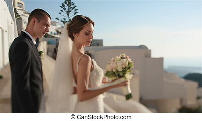 Handsome groom and gorgeous bride kissing close up with sea background