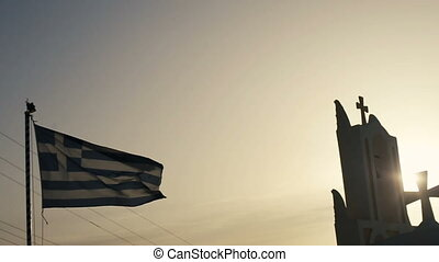Top of white church with Greek flag with blue sea at Oia, Santorini, Greece.
