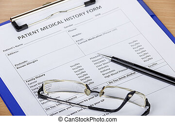 Patient medical history form on clipboard with pen and eyeglasses