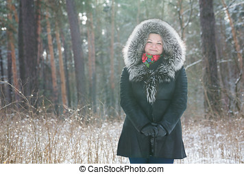 Woman saunters in the winter forest She spends free time...