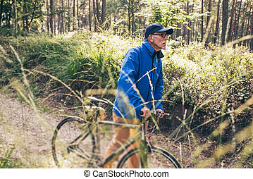Active senior man walking with bicycle on forest trail.