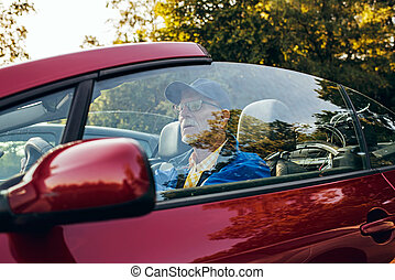 Side view of senior man sitting in sports car outdoors in...
