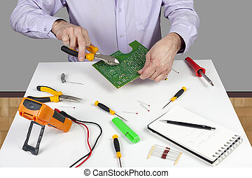 Electronic test engineer using side cutters to trim a soldered componant on PCB