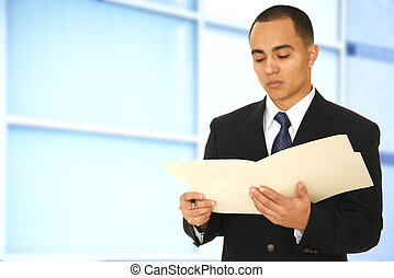 Man In Office Environment - a man reading a folder while...