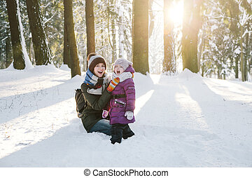 Happy mother and daughter in winter forest