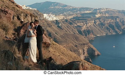 Married couple, bride and groom, kissing on mountain volcano...