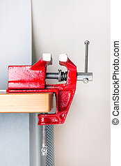 Close up view of a metal table vise clamped in a table