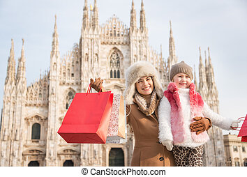 Portrait of mother and daughter with shopping bags near...