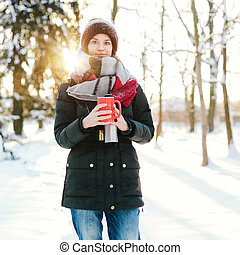 Young beautiful woman with cup in winter