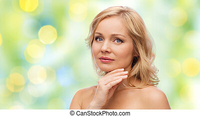 woman with bare shoulders touching face - beauty, people and...