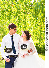 Funny bride and groom with Mr and Mrs signs. Happy wedding...