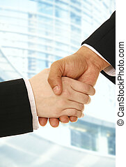 Business Deal - hand shake of business man and woman making...