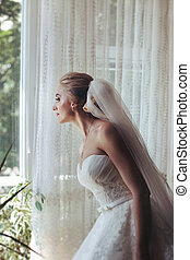 Beautiful romantic blonde bride looking out window in white...